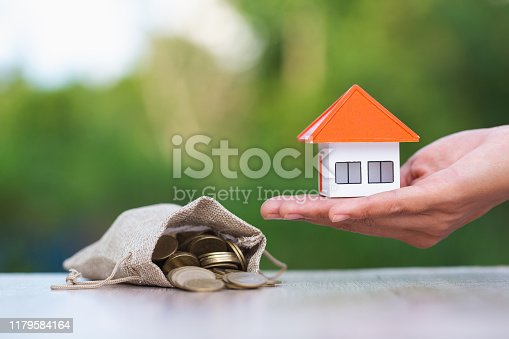 istock Home in the hands of  businessman  coin in a hemp bag Ideas of saving money for a home purchase or loan for real estate investment planning Buying a home in the future and during savings can be risky. 1179584164