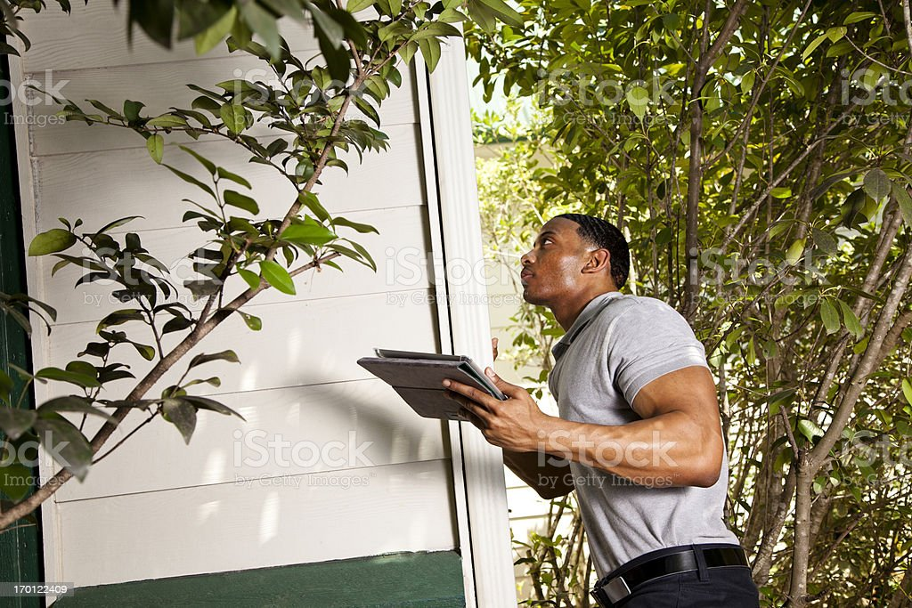 Home inspection on exterior.  Using digital tablet to record results royalty-free stock photo