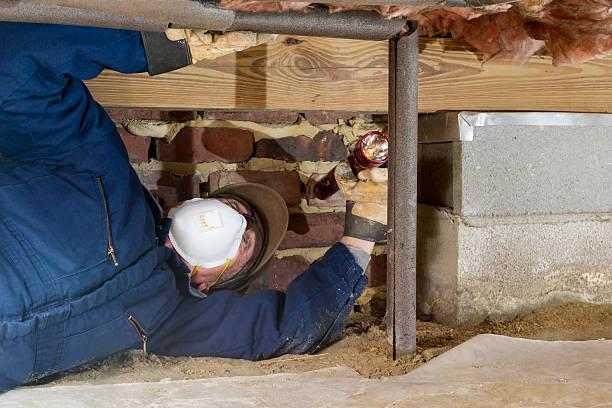 home inspector examines a freeze protected crawl space water line. - kruipruimte stockfoto's en -beelden