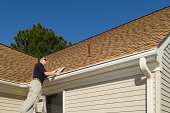 istock Home inspector examines a residential roof vent pipe. 482987099