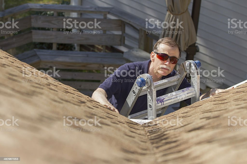 Home inspector examines architectural, asphalt shingled roof. stock photo