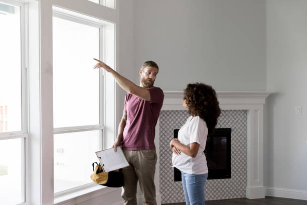 home inspector points to something outside while talking with homeowner - ispettore della qualità foto e immagini stock