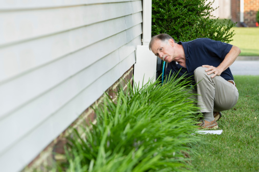 An inspector examines a home's foundation for cracks.