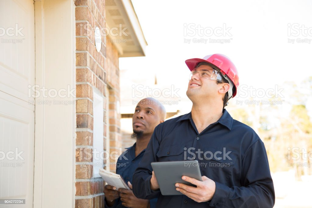 Home inspectors examine recent construction using digital tablet. stock photo