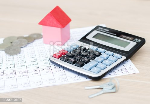 1055059750 istock photo Home insurance concept. On the table is a calculator, a model of the house and keys. Real estate. 1253710127