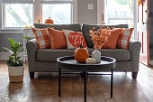 istock Home interior decorated for fall with orange accent pillows on the sofa 1279675543