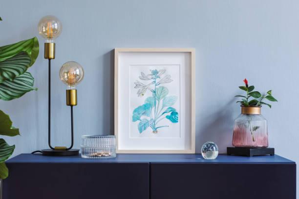 accueil intérieur floral affiche mock up avec armature en bois vertical, lampe de table, plantes, vase en verre et accessoires sur le fond du mur gris. concept avec étagère bleu marine. - camera sculpture photos et images de collection
