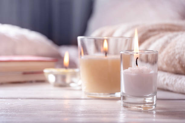 home interior. still life with detailes. several candles on white wooden table in front of bed, the concept of cosiness. - candlelight stock pictures, royalty-free photos & images