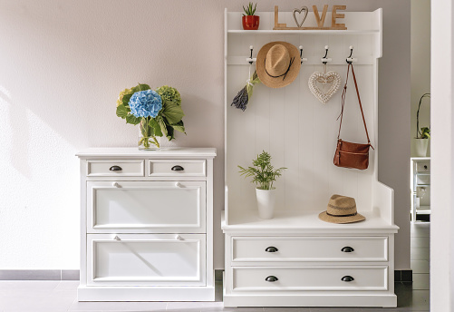 Home interior. White wooden furniture at entryway. Small foyer organisation decision.