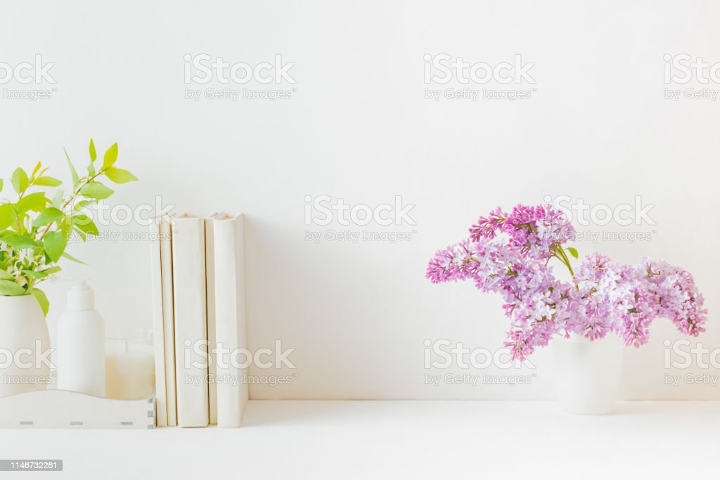 Home interior with decor elements. Book, branches of lilac in a vase,...