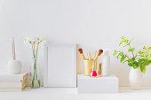 装飾要素を持つホームインテリア。白いフレーム、緑の葉が付いている枝、化粧品セット
