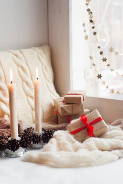 wohngebäude mit roter weihnachtsschmuck, gemütliche einrichtung und geschenk-boxen auf dem fensterbrett - schal mit sternen stock-fotos und bilder