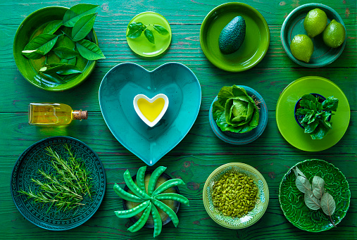 Home inventory all in green crockery plates with vegetarian food and heart shape olive oil on green