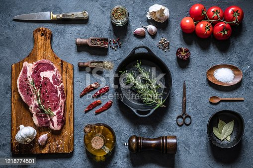 Top view of a dark gray kitchen countertop full of food and kitchen utensils for cooking and seasoning a beef steak like rosemary, bay leaf, garlic, olive oil, a kitchen knife and a cooking pan.