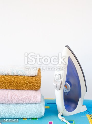 901620964 istock photo Home ironing of towels on the ironing board. Iron next to a pile of clean fresh towels Homework concept 1042424412