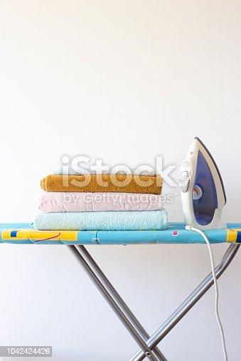 901620964 istock photo Home ironing of towels on the ironing board. Iron next to a pile of clean fresh towels Homework concept 1042424426