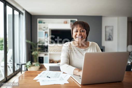Cropped portrait of a happy senior woman sitting alone and using a laptop in her living room at home