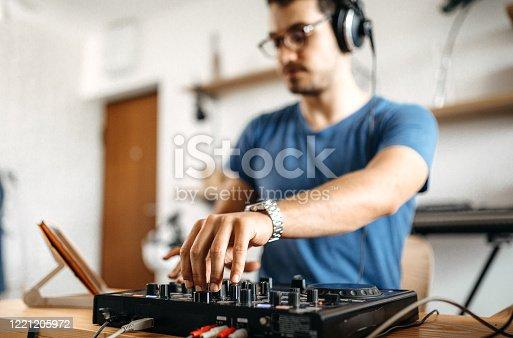 DJ using digital music mixer to produce music at home