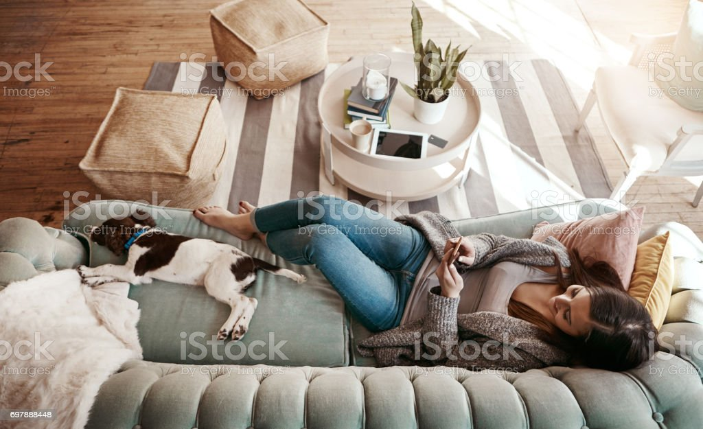 Home is the only place I want to be! Shot of an attractive young woman using her cellphone while relaxing at home 20-29 Years Stock Photo