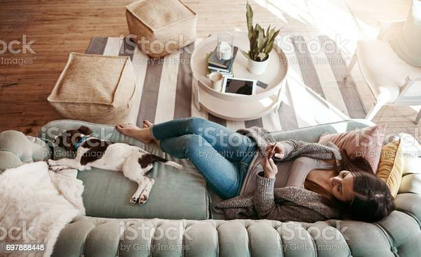 Shot of an attractive young woman using her cellphone while relaxing at home