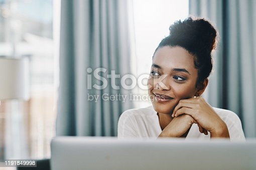 Shot of a young businesswoman looking thoughtful while using a laptop in her home office