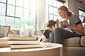 Shot of a young woman spending a relaxing day at home with her dog