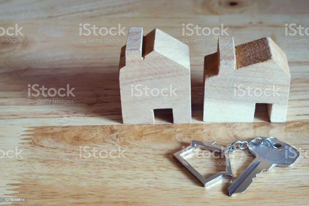 Home key with home keyring and wooden house model on bright background, real estate concept, copy space stock photo