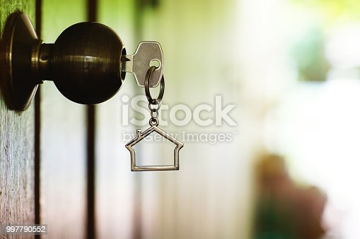 Home key with house keyring in keyhole, copy space, property concept
