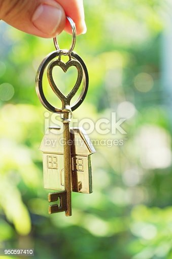 Home key with love house keyring hanging with blur garden background, free space