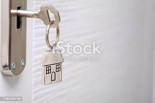 Home key with metal house keychain in keyhole