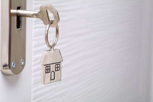 Home key with metal house keychain in keyhole stock photo