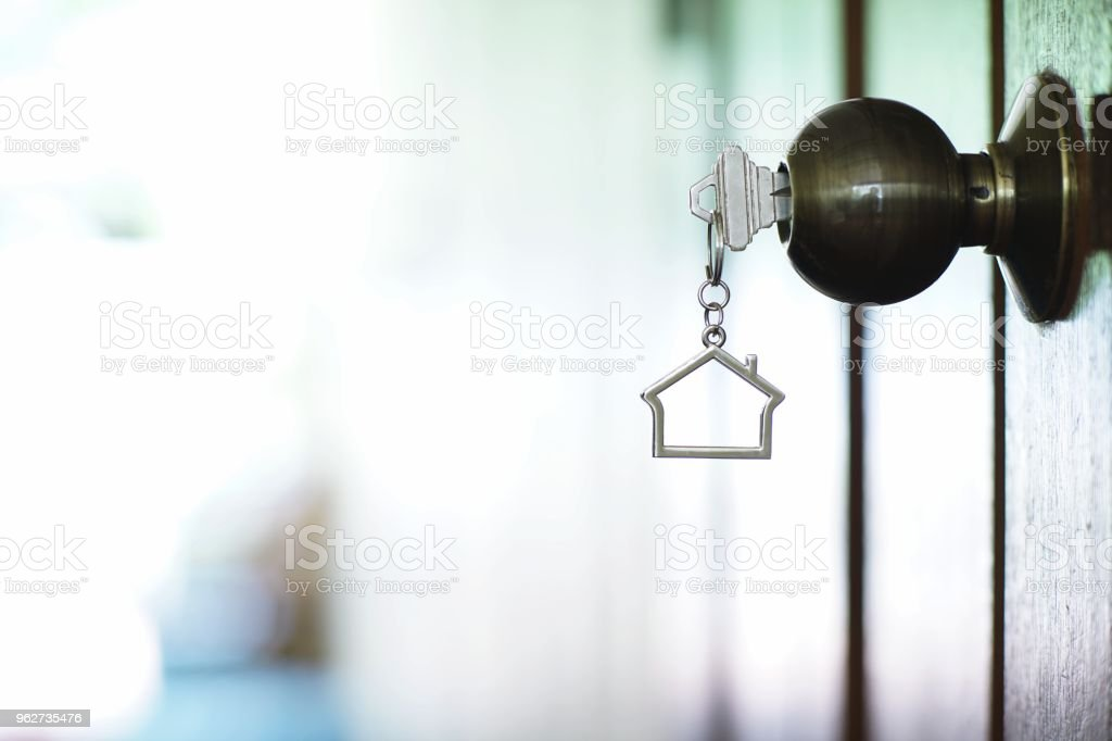 Tecla Inicio con Llavero metal casa en ojo de la cerradura, concepto de propiedad - foto de stock