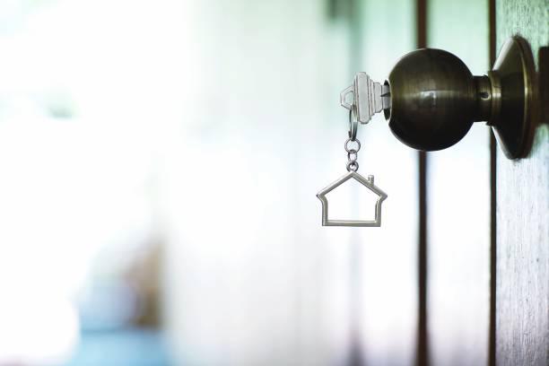 clé de maison avec maison metal keychain dans le trou de la serrure, le concept de propriété - emprunt immobilier photos et images de collection