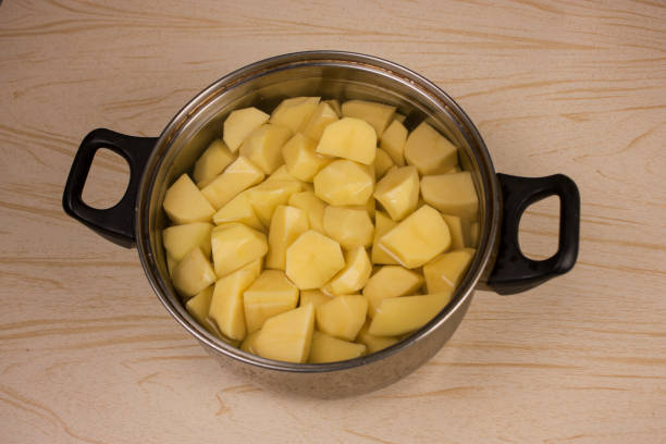 Home kitchen. A pot of peeled and chopped potatoes is on the table stock photo