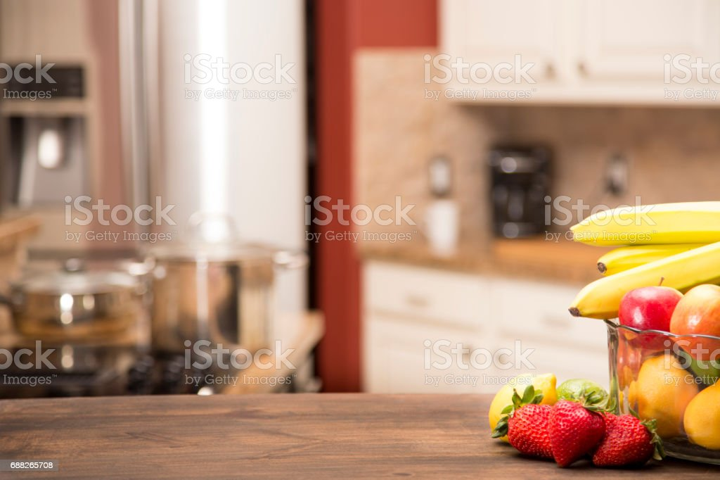 Home kitchen defocused with fruit on table in foreground. stock photo
