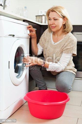istock Home laundry. mature woman using washing machine 491066773