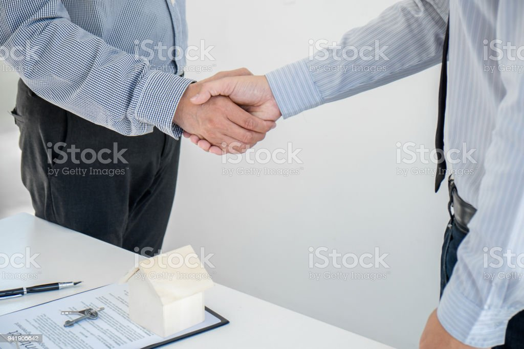 Home loan insurance concept, broker agent shaking hands with customer after good deal agreement, home model stock photo