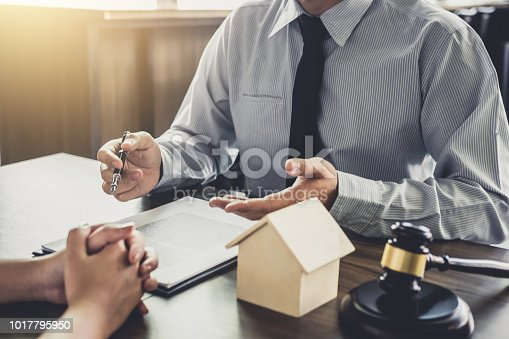 941906652 istock photo Home loan insurance, Male lawyer or judge Consult with client and working with Law books, report the case on table in office, Law and justice concept 1017795950