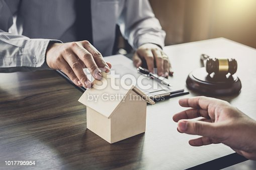 941906652istockphoto Home loan insurance, Male lawyer or judge Consult with client and working with Law books, report the case on table in office, Law and justice concept 1017795954