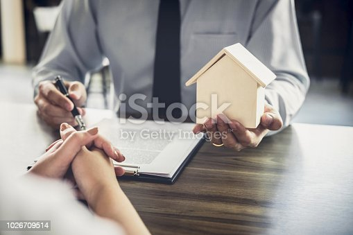 941906652istockphoto Home loan insurance, Male lawyer or judge Consult with client and working with Law books, report the case on table in office, Law and justice concept 1026709514
