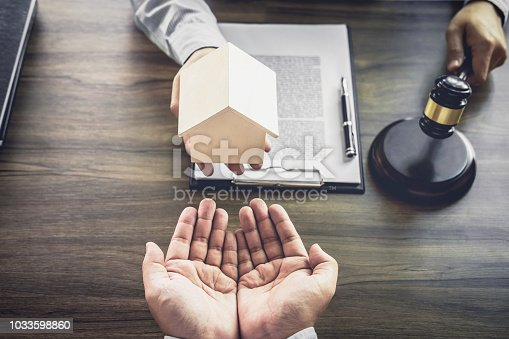 941906652 istock photo Home loan insurance, Male lawyer or judge Consult with client and working with Law books, report the case on table in office, Law and justice concept 1033598860