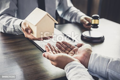 941906652 istock photo Home loan insurance, Male lawyer or judge Consult with client and working with Law books, report the case on table in office, Law and justice concept 946925000