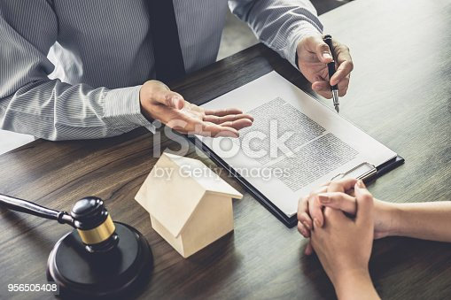941906652 istock photo Home loan insurance, Male lawyer or judge Consult with client and working with Law books, report the case on table in office, Law and justice concept 956505408