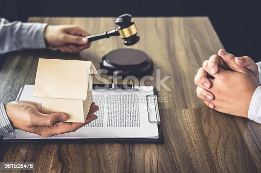 941906652 istock photo Home loan insurance, Male lawyer or judge Consult with client and working with Law books, report the case on table in office, Law and justice concept 961528478