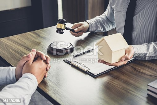 941906652istockphoto Home loan insurance, Male lawyer or judge Consult with client and working with Law books, report the case on table in office, Law and justice concept 981420258