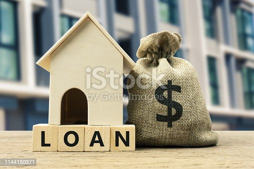istock Home loan, mortgage, home insurance, financial mortgage for house concept. A dollar money in bag and residential model on a wooden block. 1144150371