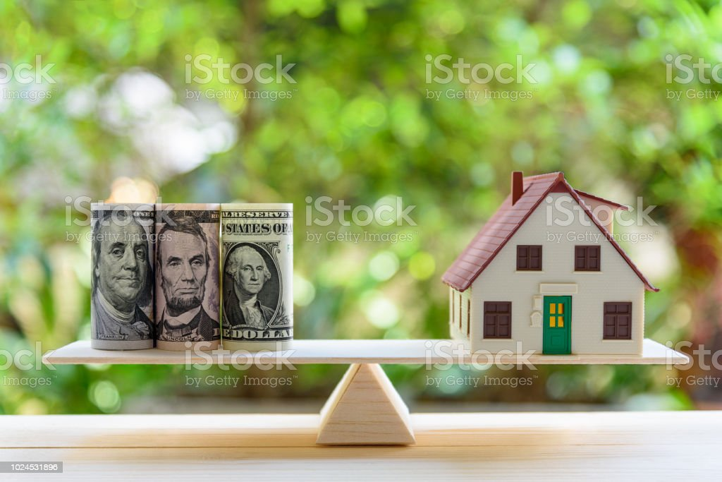 Préstamo / inversa hipoteca o transformación de bienes en concepto de efectivo: la casa modelo, notas de dólar de los E.E.U.U. en una escala de equilibrio simple, representa a un propietario o un prestatario da propiedades / residencia en dinero en efec - foto de stock