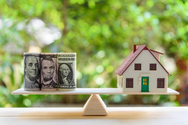 Home Darlehen / Hypothek oder Umwandlung von Vermögen in Bargeld Konzept umkehren: hausmodell, US-Dollar-Noten auf eine einfache Balance-Skala zeigt einen Eigenheimbesitzer oder ein Kreditnehmer dreht Eigenschaften / Residenz in Bargeld – Foto