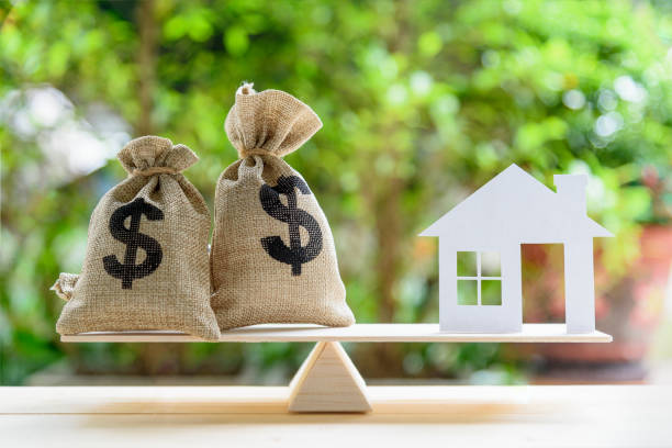 Home loan / reverse mortgage or transforming assets into cash concept : House paper model , US dollar hessian bags on a wood balance scale, depicts a homeowner or a borrower turns properties into cash Home loan / reverse mortgage or transforming assets into cash concept : House paper model , US dollar hessian bags on a wood balance scale, depicts a homeowner or a borrower turns properties into cash borrowing stock pictures, royalty-free photos & images
