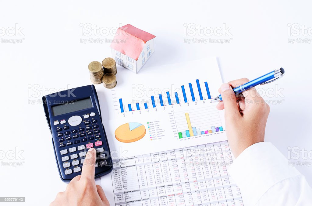 Home loans concept with hand holding calculator with business document chart stock photo